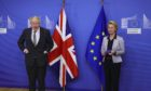 Britain's Prime Minister Boris Johnson is welcomed for a dinner with European Commission president Ursula von der Leyen, right, in Brussels.