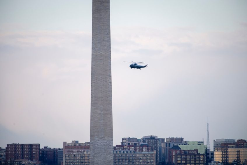 Marine One carrying President Donald Trump flies by the Washington Monument as it departs from the White House in Washington.