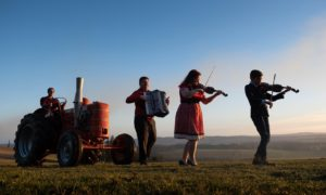 Musicians Alan Small, Gemma Donald and 10-year-old Andrew Farquharson with farmer Clark Farquharson at the wheel of 1956 Field Marshall tractor.  ....Pic Paul Reid