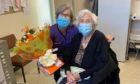 Edith Dean receives birthday flowers from Westgate Medical Practice nurse Valerie Dowds Christie