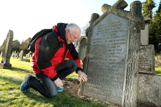 Local researcher Steve Nicoll at the Gray family headstone in Brechin cemetery.