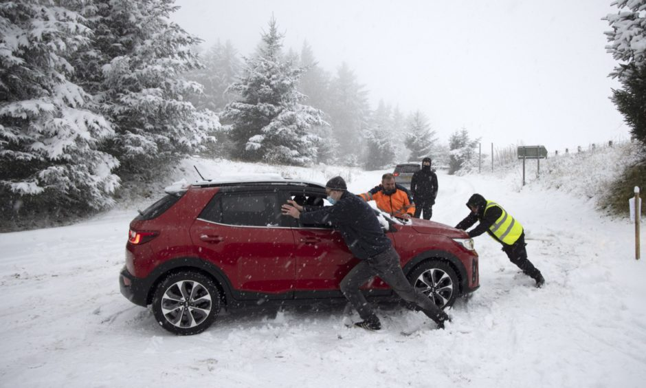 Passersby help a NHS worker stuck in the snow at the junction between the A9 and the road to Findo Gask.