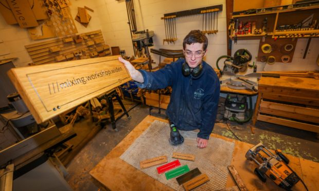 Bailey Pearce (workshop technician) with examples of the signs at The Workshop Aberfeldy.