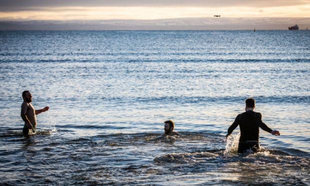 New Year Dookers Andrew Davies (36), John Wilson (35) and Davie Frew (30) make a splash at Ravenscraig Beach in Kirkcaldy.