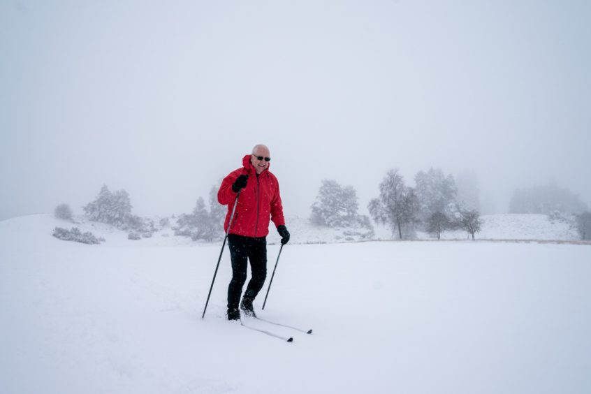Douglas Hamilton, who was supposed to tee off at 9.50am, finds another means of exercise as he skis around the golf course at Gleneagles this morning.