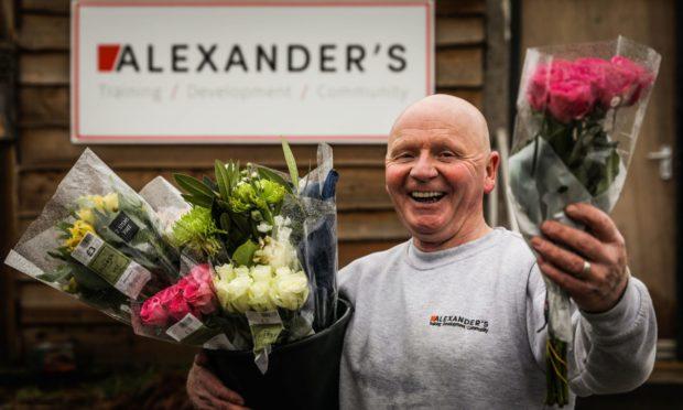 John Alexander, of Alexander's Community Development, with free flowers.