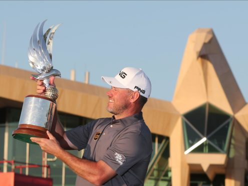 Lee Westwood surveys the trophy under the steely glare of the Abu Dhabi clubhouse eagle.