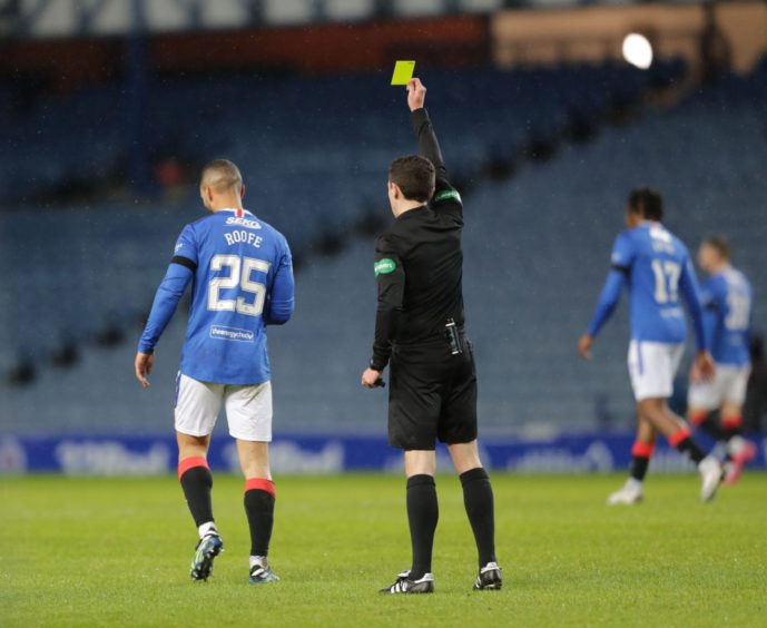 David Munro shows Kemar Roofe a yellow card.