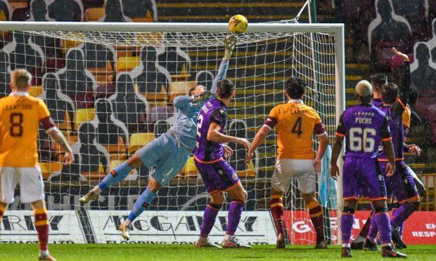Benjamin Siegrist makes a big save from Motherwell defender Bevis Mugabi.