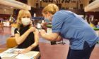 Margaret Scott receiving her vaccination at the Caird Hall from vaccinator Suzy Black.