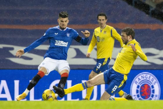 Rangers' Ianis Hagi (L) is tackled by St Johnstone's Murray Davidson.