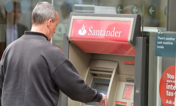 A man using a cash machine outside a branch of Santander.