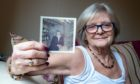 Alison Sibbald with a photo of her brother, who wrote the message more over 55 years ago.