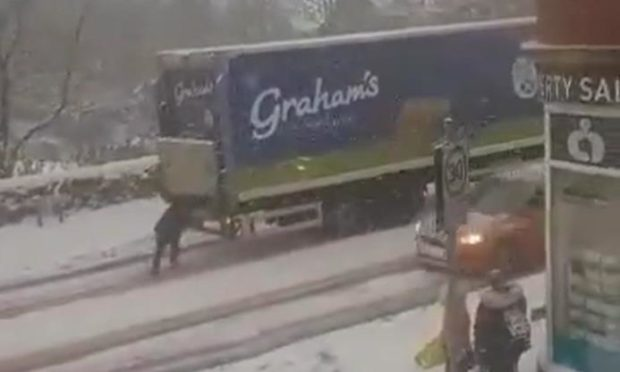 A woman appears to be 'pushing' a lorry up a snow-covered hill in Cowdenbeath.