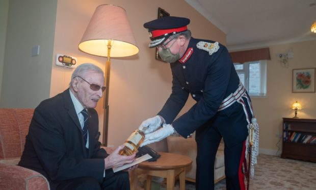 Lord Lieutenant Stephen Leckie delivers a bottle of whisky and a letter from Prince Charles to 100 year old WWII veteran Ernie Holmes at Kincarrathie House in Perth