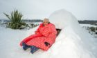 Delilah Frampton, all wrapped up outside her igloo.