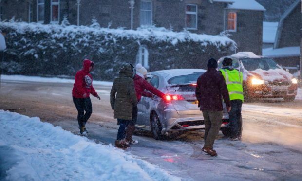 Good Samaritans helping to push cars on an icy curve of Glasgow Road, Perth. Pic: Steve MacDougall