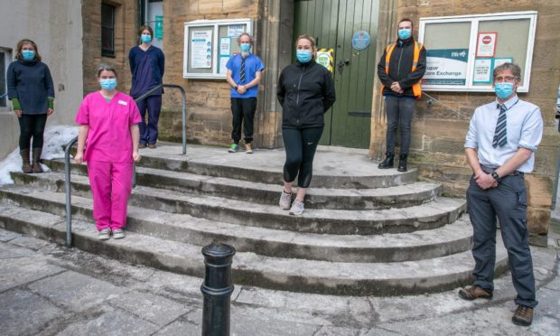 Cupar doctors, Sara McQuitty, Callum Duncan, Kirsty McQuitty, Steven Macfarlane, Hannah Dakin and former Bell Baxter pupils, Sean Colgan (High Vis) and Tara Gibson (front centre) at the Cupar Corn Exchange where they are vaccinating people from Covid-19 on Saturday.