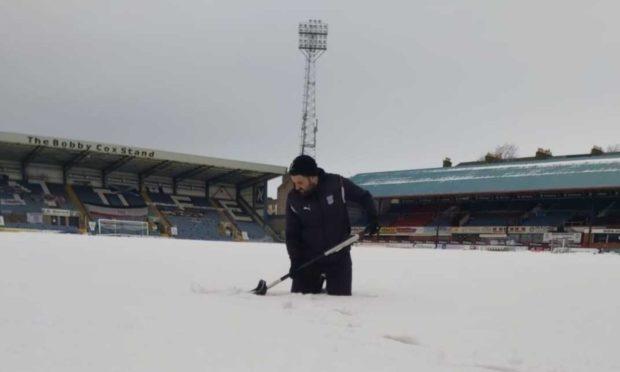 Dundee assistant groundsman Brian Robertson Jnr battles through the snow at Dens Park