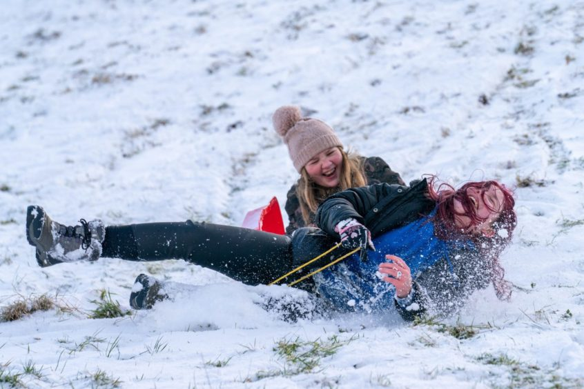 Erin McCormack (13) and Abi Grieve (12) race down the slopes in Newburgh, Fife.