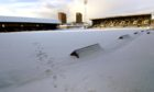 A library photo showing Dens Park covered in snow in 2014.