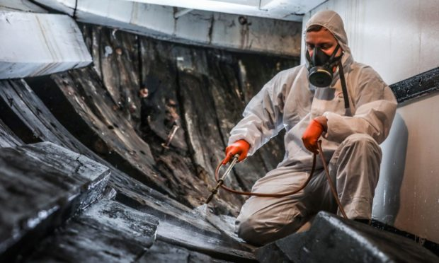 The Evening Telegraph, CR0026772, News, workers from Intona (joinery firm) are carrying out some works free of charge on the RSS Discovery to preserve the ship. Picture shows; Technician Stuart Dalzell sprays the ship  to help preserve her. Tuesday 23rd February, 2021. Stuart Mhairi Edwards/DCT Media