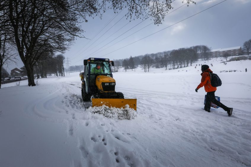A mini snow plough clears the paths in a park on South Road, Lochee.