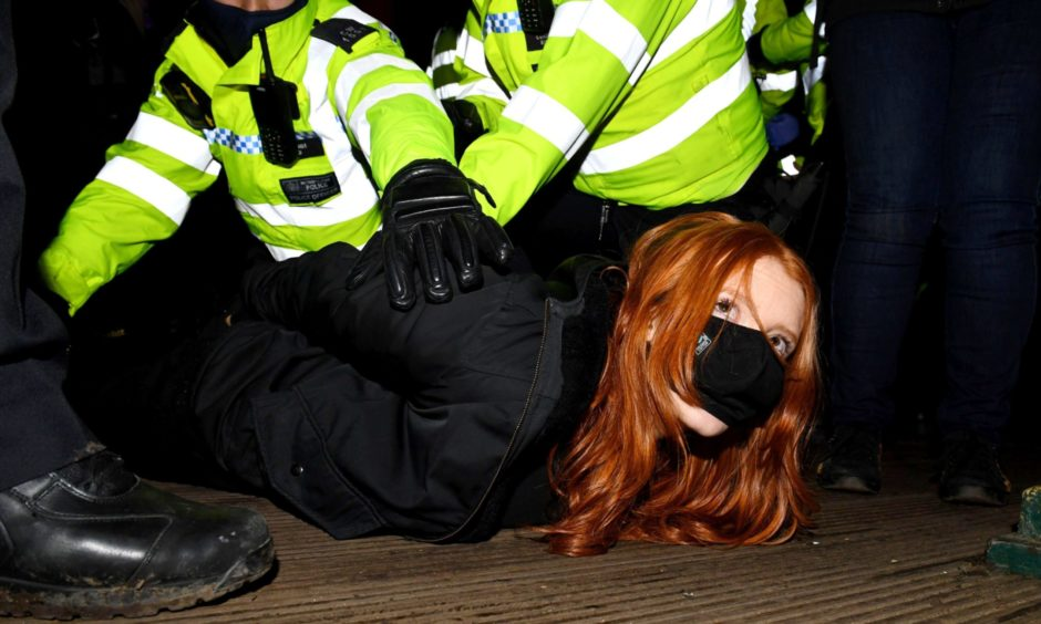 A woman is arrested at a vigil in memory of Sarah Everard, Clapham, London.