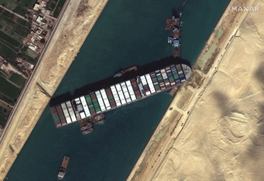 A satellite image made available by MAXAR Technologies shows tug boats positioned alongside the Ever Given in the Suez Canal on March 27.