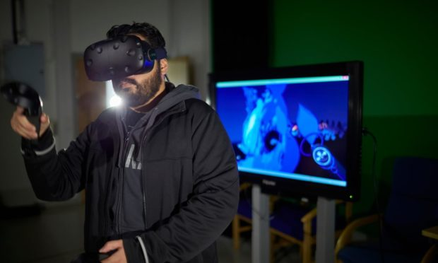 An Abertay University video game student trying out a VR headset.