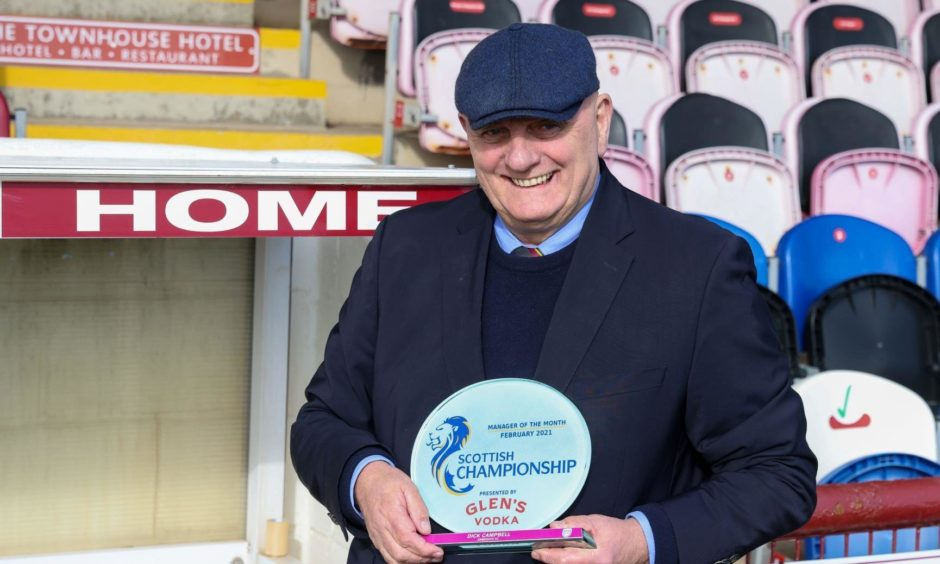 Dick Campbell holding the Scottish Championship Manager of the Month trophy