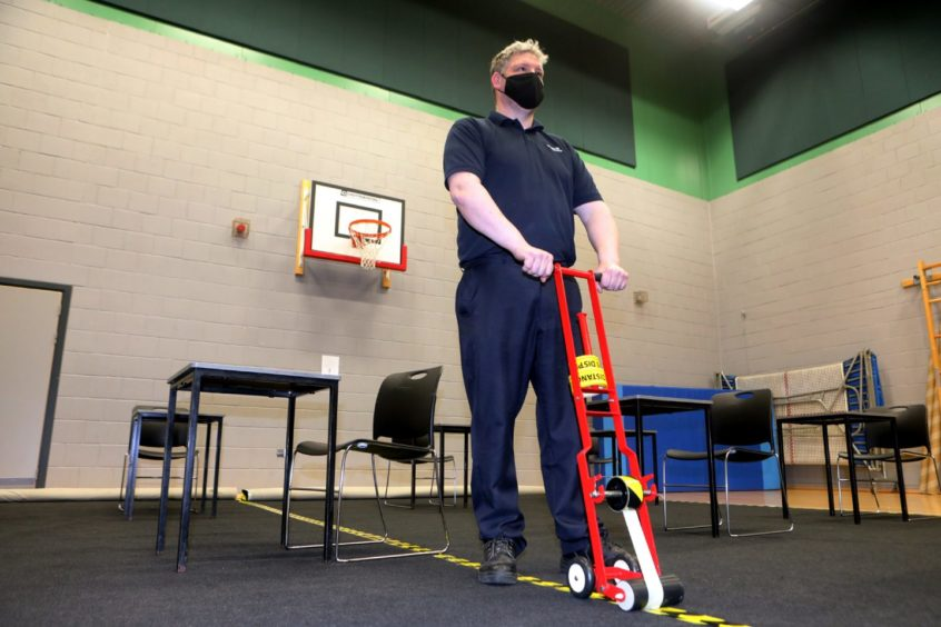 Head caretaker Brian Smith puts down the social distance tape in the gym hall.