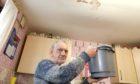 Robert Heath underneath his leaking kitchen ceiling