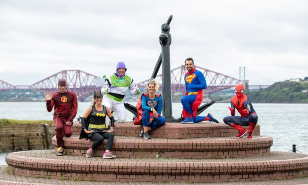 Courier News - Fife - Neil Henderson story - CR0022081 - local west Fife lockdown 'superheros' who will be running together through the streets of Dalgety Bay to entertain kids. Picture shows; the superheroes at the Anchor Monument - l to r - 'Flash' Geoff Nicholson, 'Batwoman' Carol Quoi,  'Buzz Lightyear' Andy Spence, 'Superwoman' Debbie Miller, 'Superwoman' Debbie Miller, 'Superman' Nick Green and  'Spiderman' Dave Roper, Harbour Drive, Dalgety Bay, 28th June 2020, Kim Cessford / DCT Media.