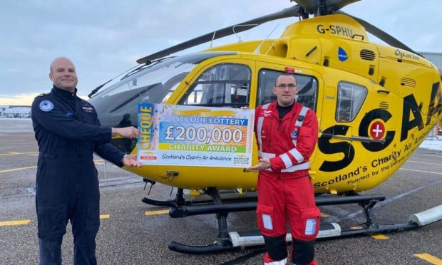 SCAA pilot Captain Pete Winn and lead paramedic Ewan Littlejohn with the latest funding award from People's Postcode Lottery.