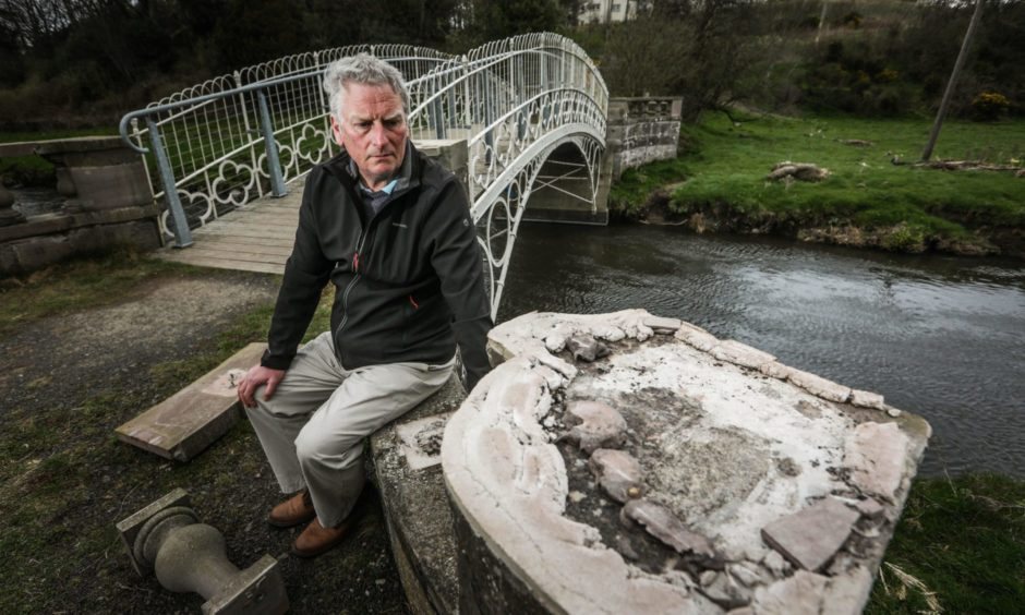Councillor Craig Duncan next to the damaged stonework.