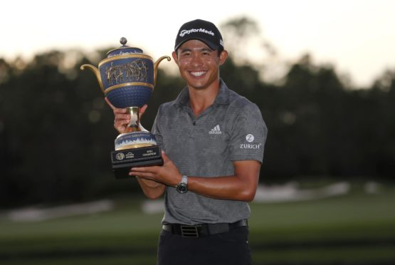 Collin Morikawa of the US celebrates with the WGC trophy.
