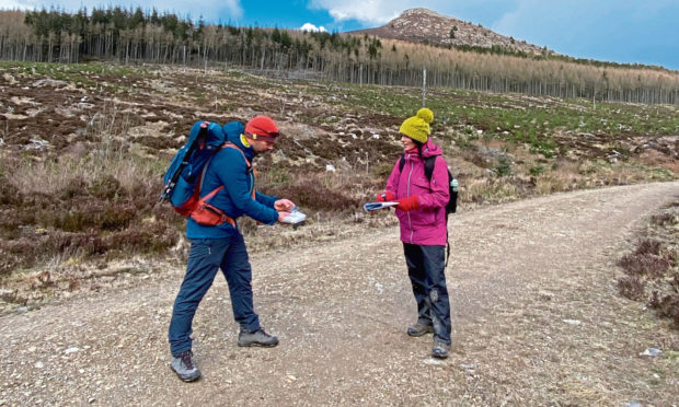 Hillgoers founder Garry Cormack shows Gayle how to navigate on a trip exploring Bennachie.