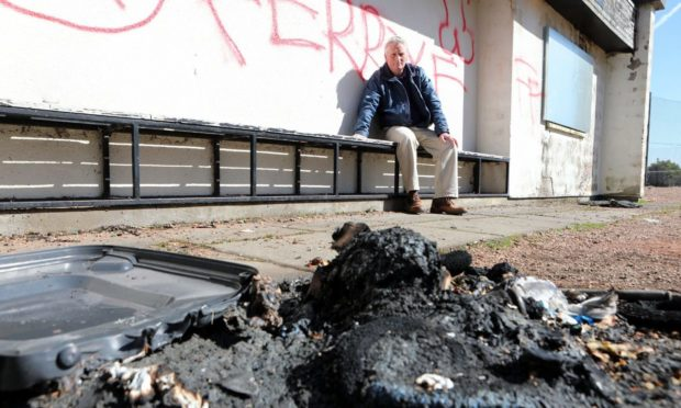 Craig Duncan with graffiti and fire damage at the Broughty Ferry pavilion.