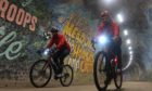 Mark Beaumont and Markus Stitz cycling through a tunnel in Edinburgh.