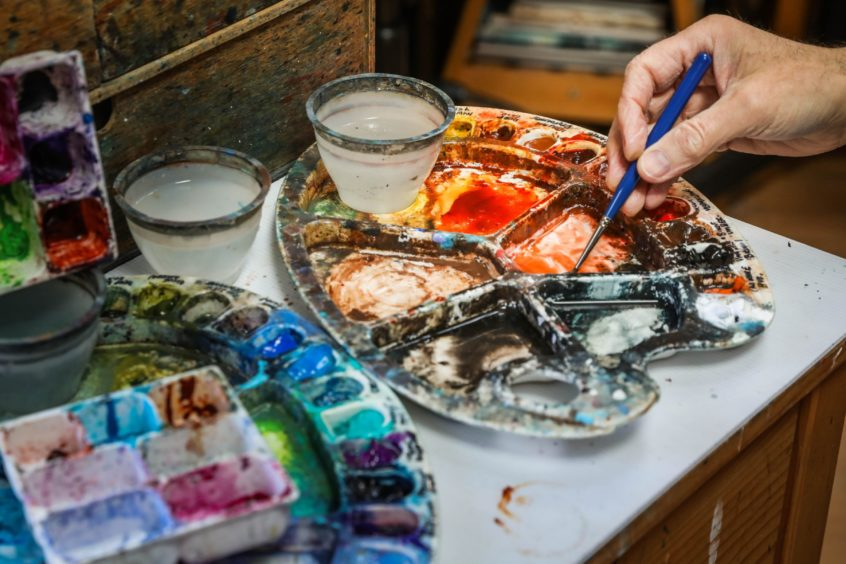 Up close: Angus mixes his paints.