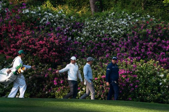 Justin Thomas and Rory McIlroy in practice with azalea backdrop at Augusta.