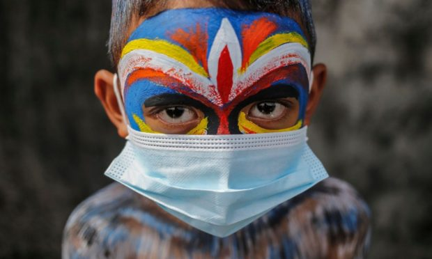 Mandatory Credit: Photo by Johanes Christo/NurPhoto/Shutterstock (11911198k) Balinese have their bodies painted during sacred Ngerebeg ritual amid COVID-19 pandemic at Tegallalang Village in Gianyar, Bali, Indonesia on May 19 2021. Ngerebeg is a sacred ritual held every six month which is believed to expel bad luck and evil spirits. The participants decorates their bodies with colourful paints and accessories to symbolise astral beings while marching across the village. Bali Sacred Ngerebeg Ritual Amid COVID-19 Pandemic, Gianyar, Indonesia - 19 May 2021