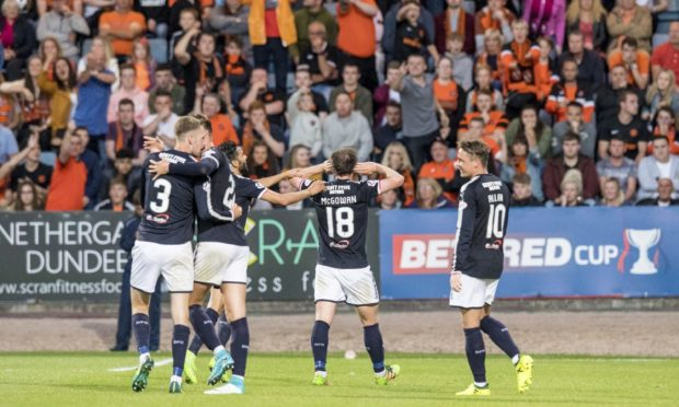 Paul McGowan celebrates in front of Dundee United fans.