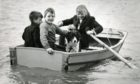 Children are joined by a collie on a boat at the Swannie Ponds back in 1964.