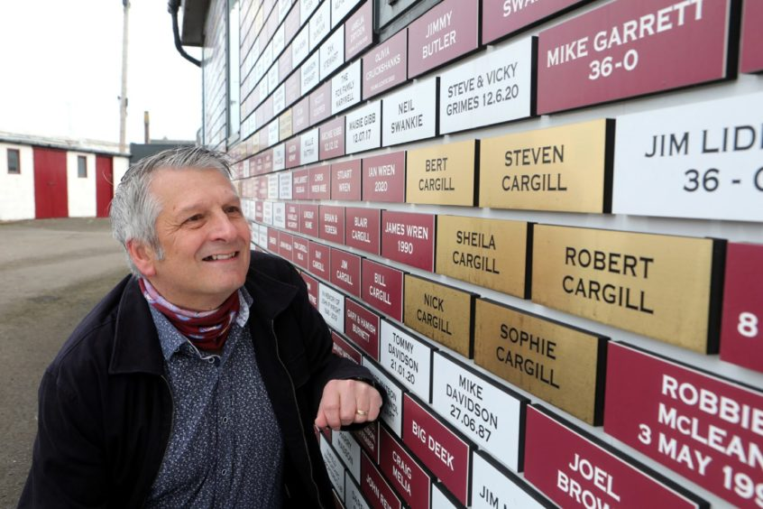 Arbroath chairman Mike Caird looking at names on the Arbroath supporters wall