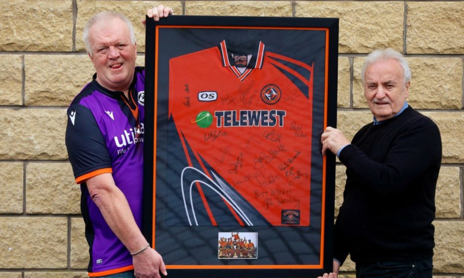 Ronnie Taylor and Davie Mack with the shirt which is taking pride of place in Club 83.