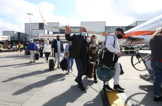 Passengers board a flight to Portugal at Gatwick on Monday.