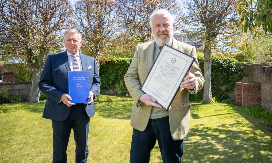 Former club president, Robert Dunn and club president, Clive Murray are seen with the Founder Members Book of Minutes and the club's charter certificate which was presented in 1922.