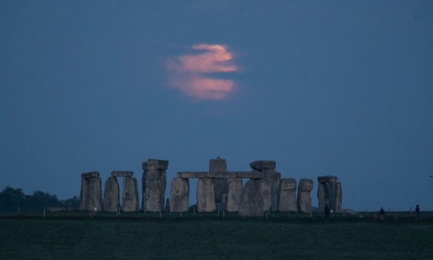 The Flower supermoon sets behind Stonehenge in Wiltshire. Picture date: Wednesday May 26, 2021. PA Photo. Being only 357,462 km away from Earth, the Moon will appear a whole 30 per cent brighter and 14 per cent larger than some previous full Moons.  Photo credit should read: Andrew Matthews/PA Wire